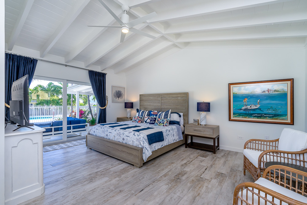 King master bedroom suite with seating, TV, and private access to patio overlooking the private pool at marathon Florida vacation rental