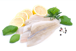 fresh fish filet, lemon slices and basil leaves
