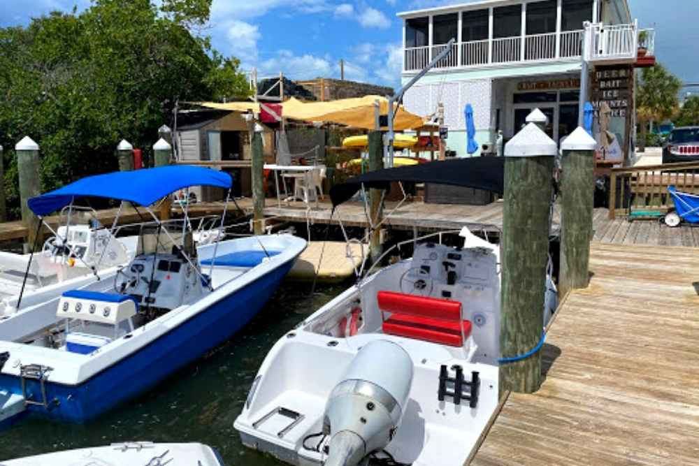 2 boats tied up at the dock in front of a boat rental shop in marathon, florida