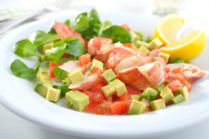 Lobster bites, greens, avocado cubes, and lemon wedges served on a white plate in marathon florida
