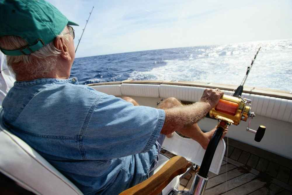 Elderly man sitting in boat facing the ocean deep sea fishing in the Florida Keys