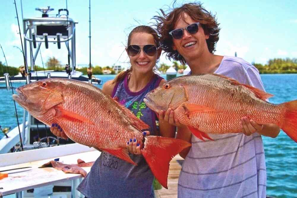 Woman and Man couple each holding a red snapper fish in the Florida Keys