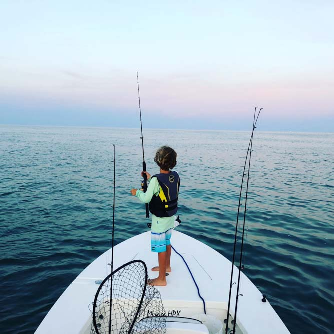 Boy holding fishing rod standing at the  bow facing the ocean at sunset in Florida Keys