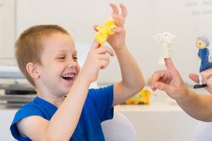 teacher showing young student finger puppets