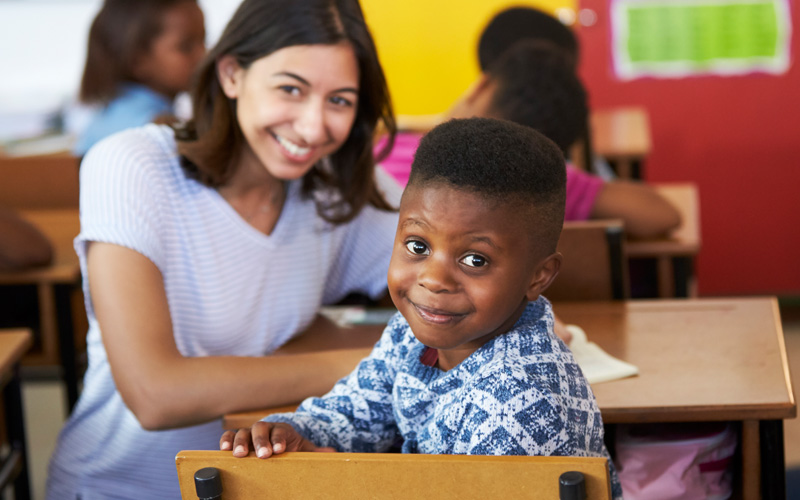 smiling young boy looking at the camera with a young woman volunteer in the background