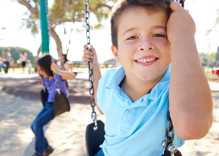 young boy smiling on a swing set
