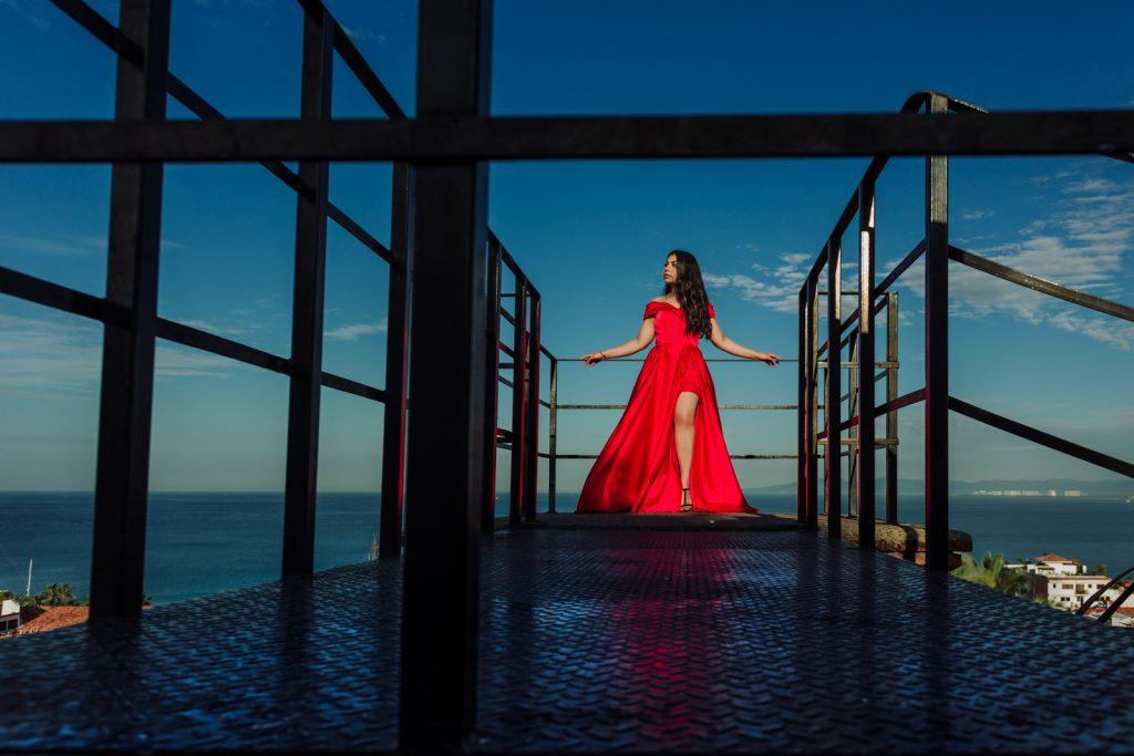 bride looking red dress ocean sky