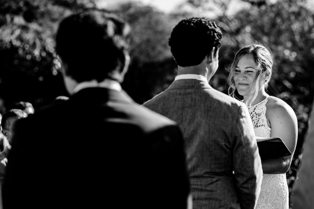 bride say the vows during the ceremony with a book on the hands