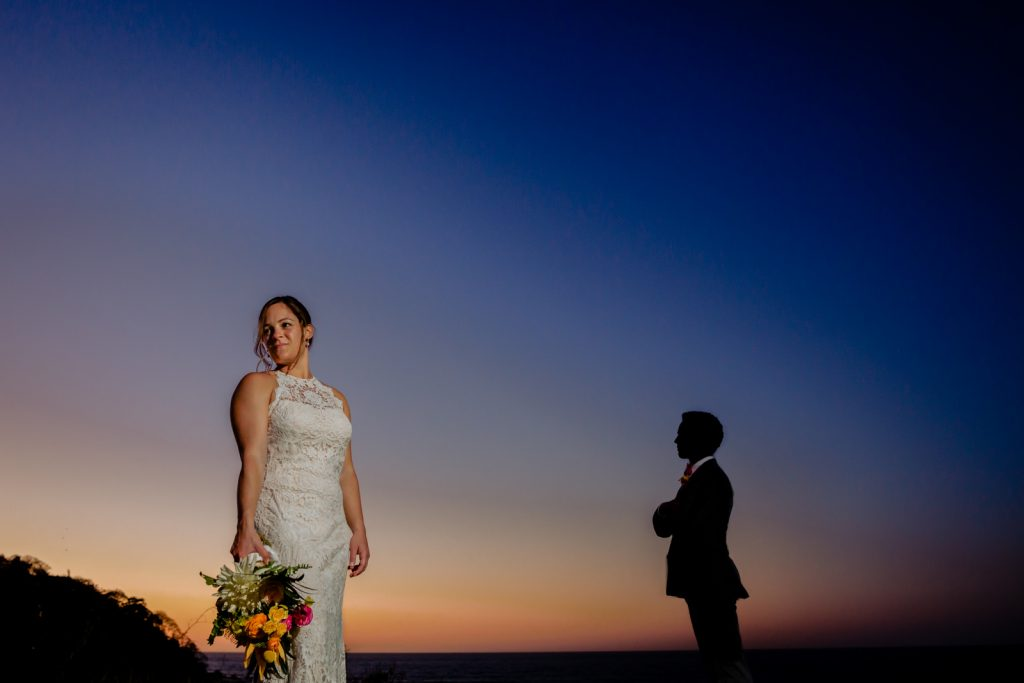 bride and groom at sunset the bride are holding flowers and the groom is in the background