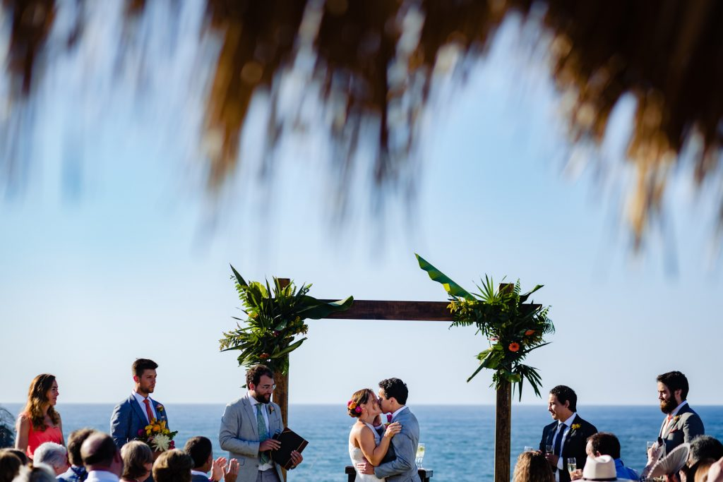 bride and groom kissing during the ceremony  with the ocean on the background and the guest looking at them