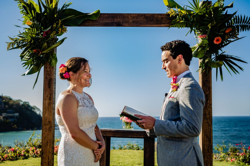 bride and groom during the ceremony with the vows with the ocean in the background
