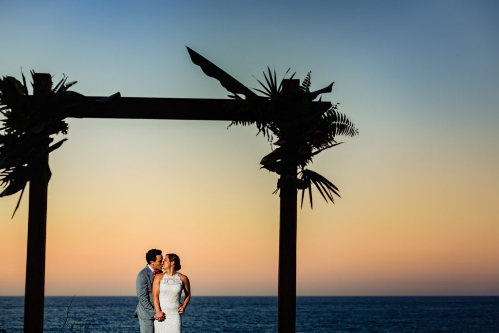 bride and groom kissing during the sunset with the ocean on the background