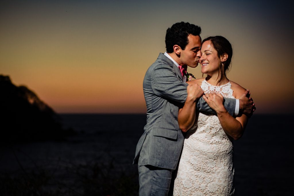 bride and groom hugs at the sunset  the groom kiss her and the bride smile