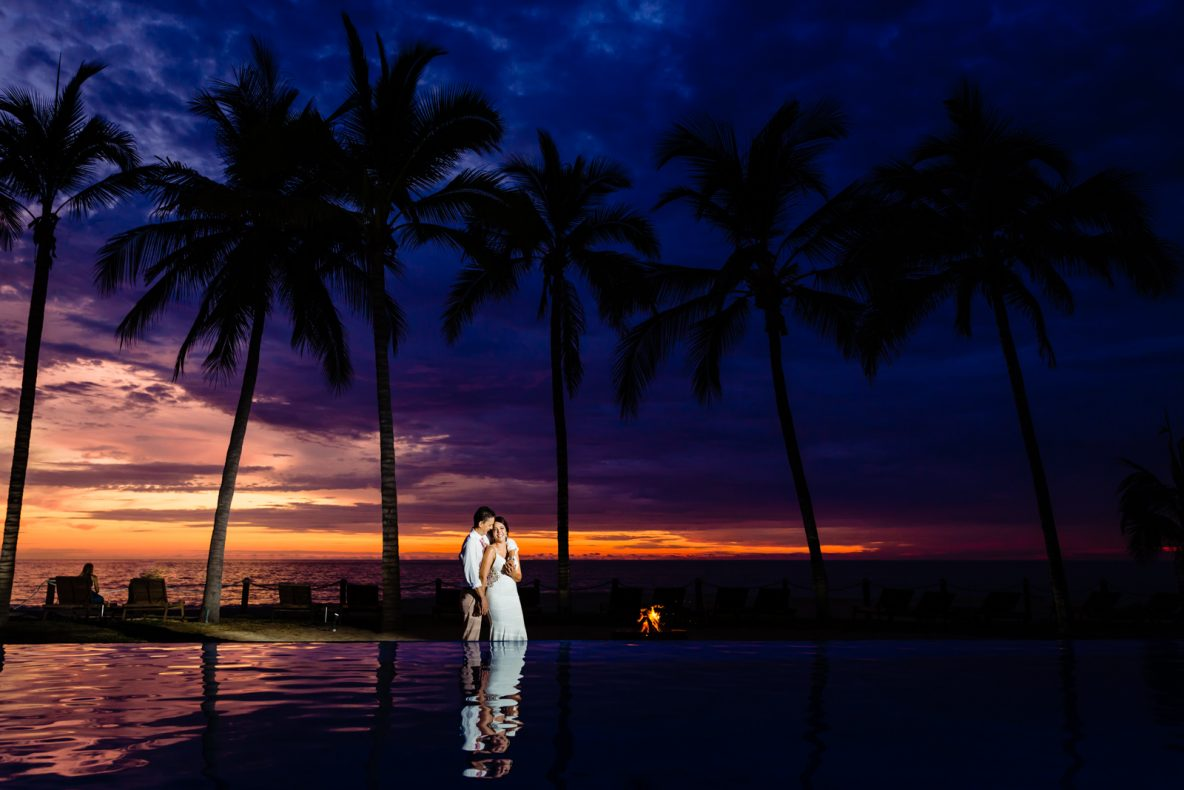 wedding, bride and groom on the beach with sunset on the background, couple smiling