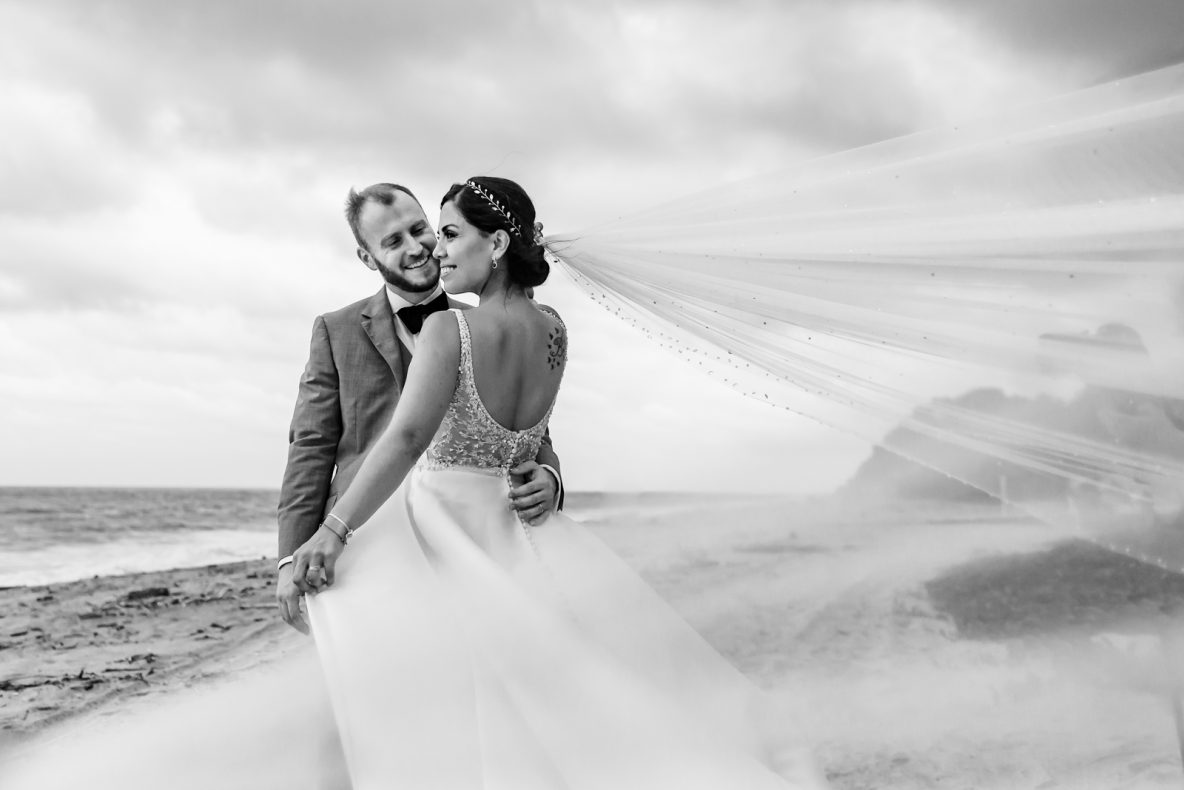 bride and groom on the beach play with the veil