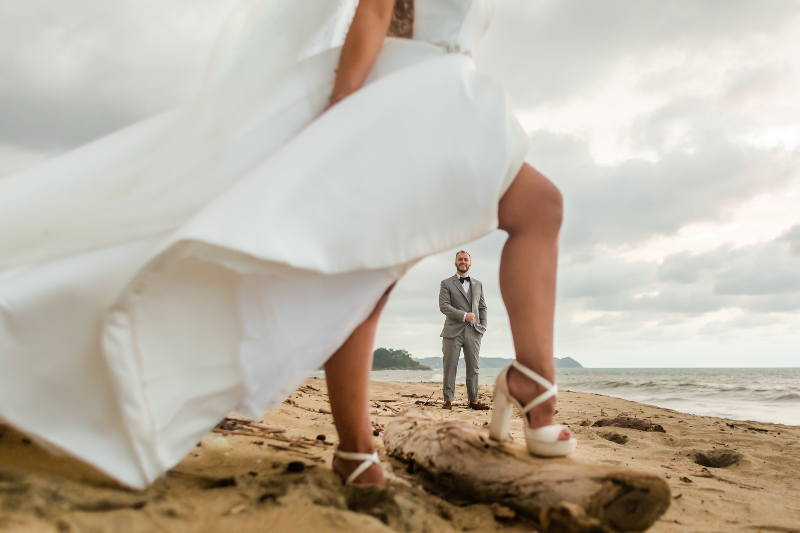 wedding bride and groom groom between the legs, wedding white dress, beach and ocean
