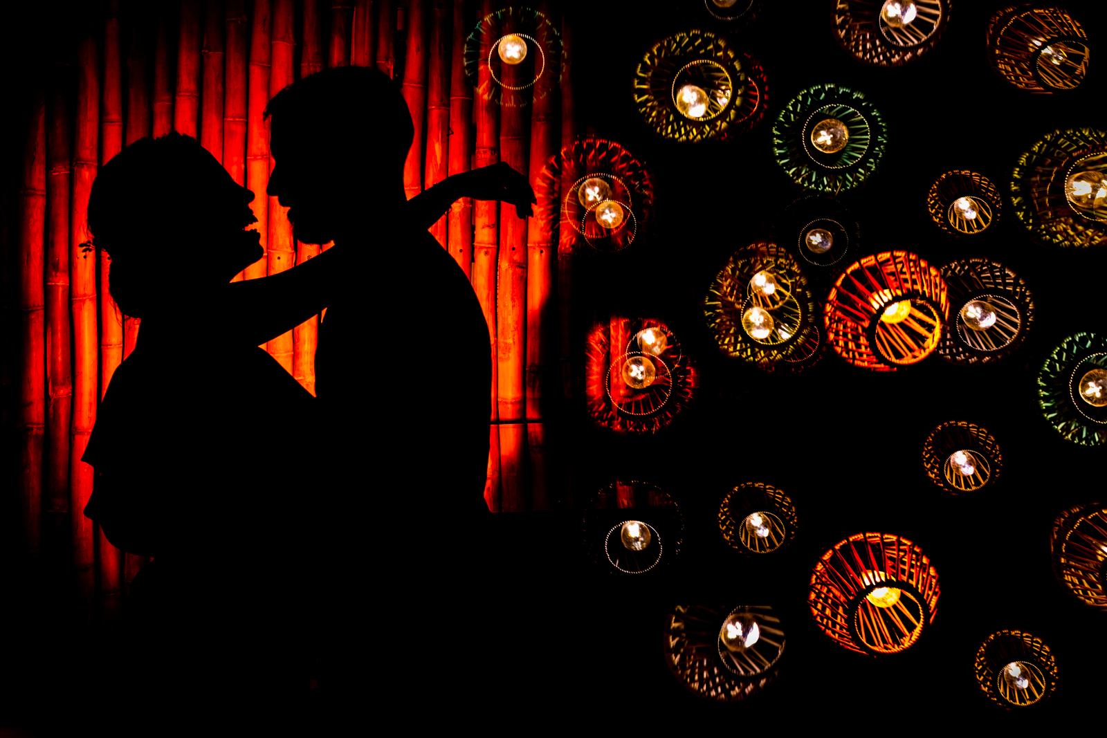 silhouette light bride and groom red wall, bride smile