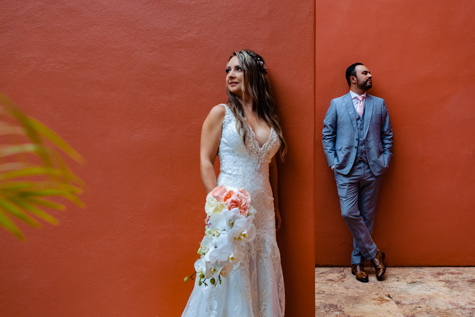 bride and groom on a red wall
