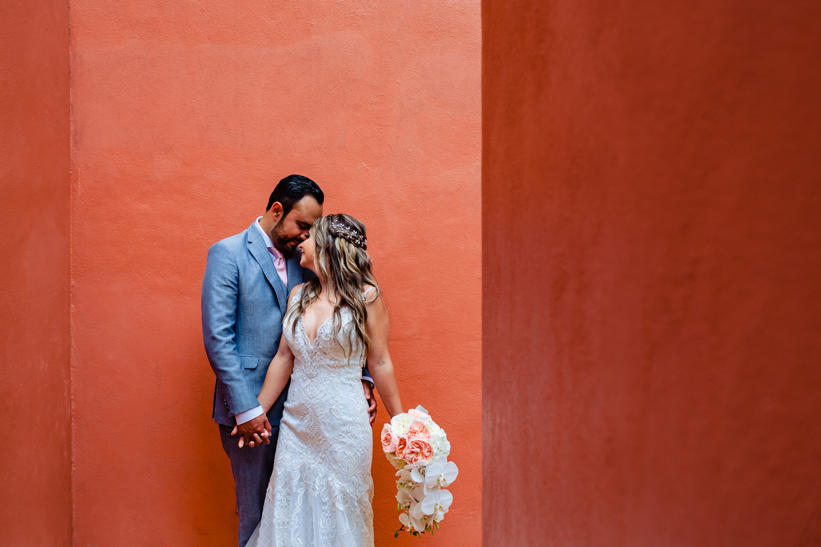 bride and groom hugs and touch his face on a red wall