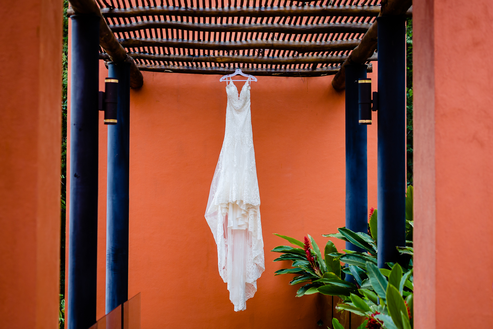 wedding dress hang on a red wall during a gettin ready