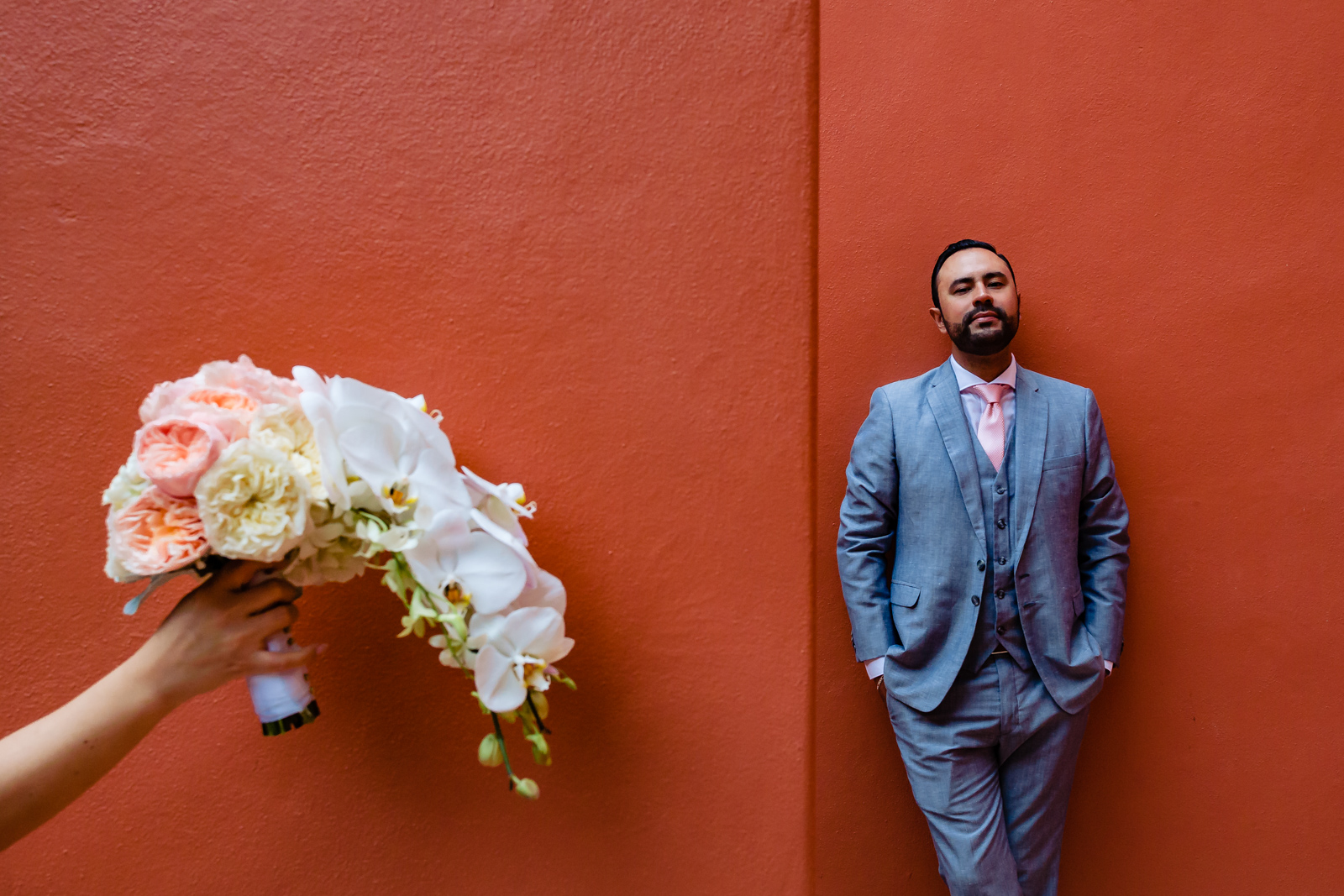 flowers and groom on a red wall
