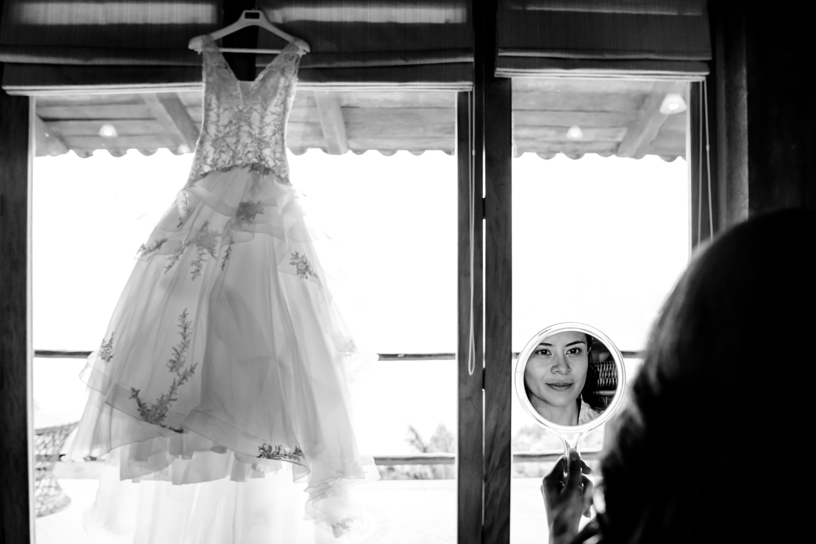 bride look in the mirror with the dress hang on the windows