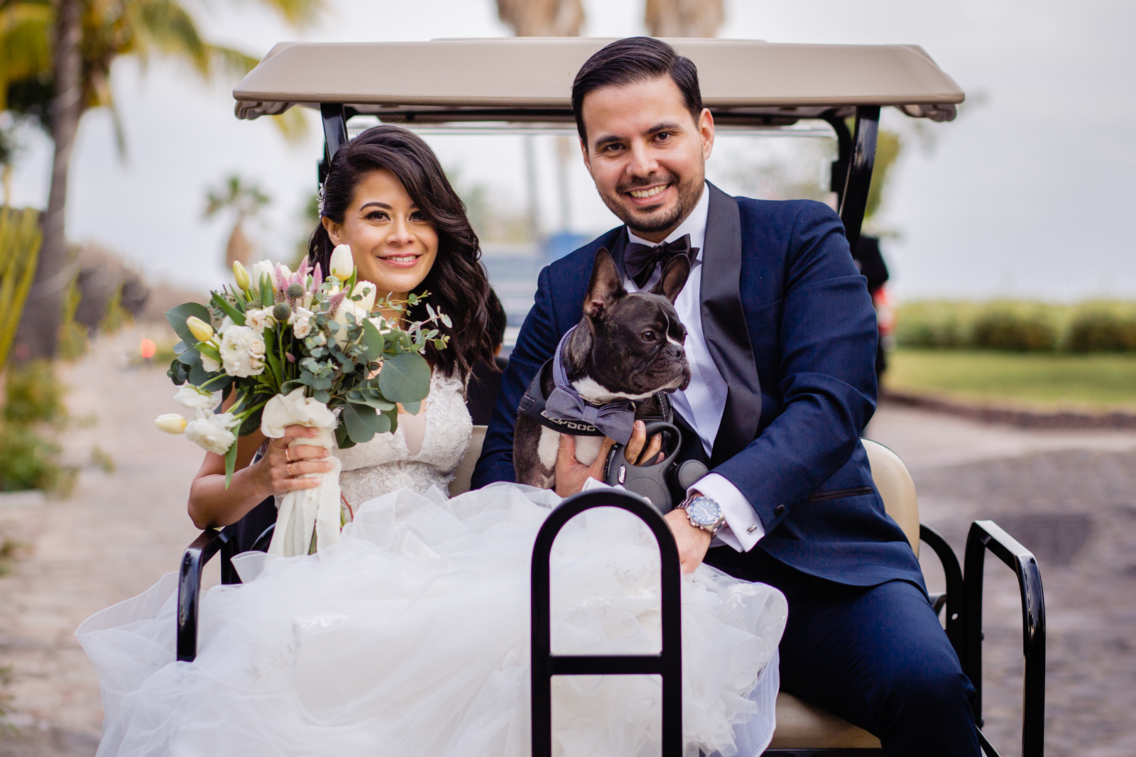 bride and groom at the end of the ceremony on a golf cart with the lovely dog
