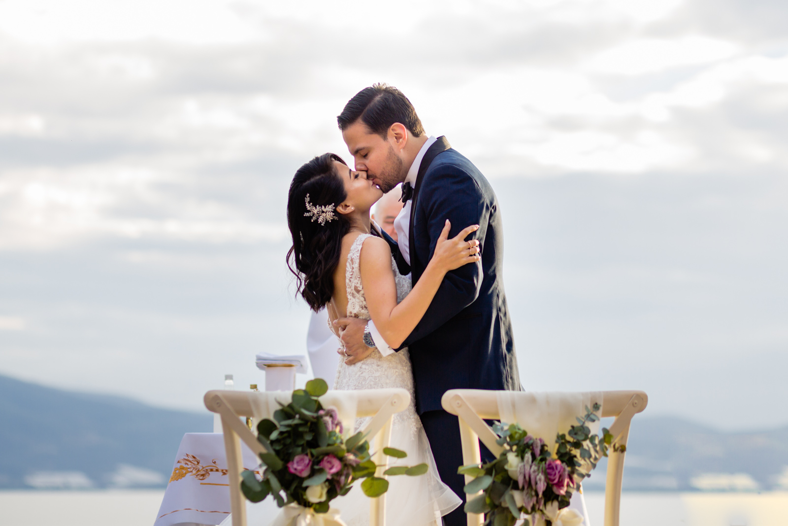 bride and groom first kiss during the ceremony with the lake on the background