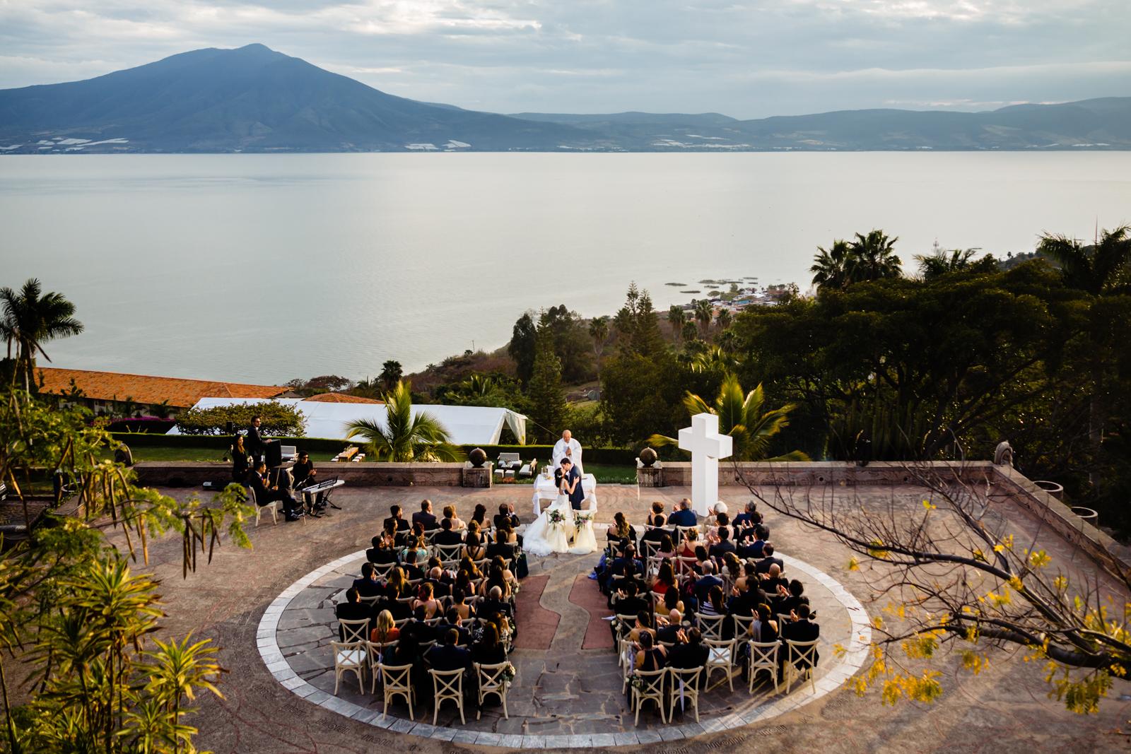 wedding on Chapala lake, bride and groom kissing with lake on the background