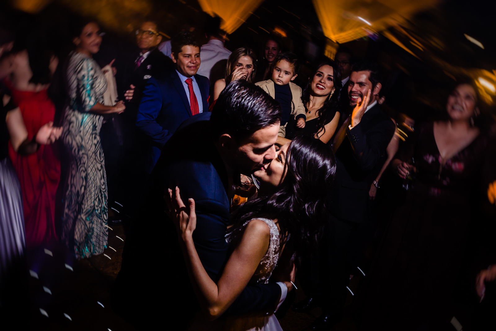 bride and groom kiss with all the friends behind them on the dance floor