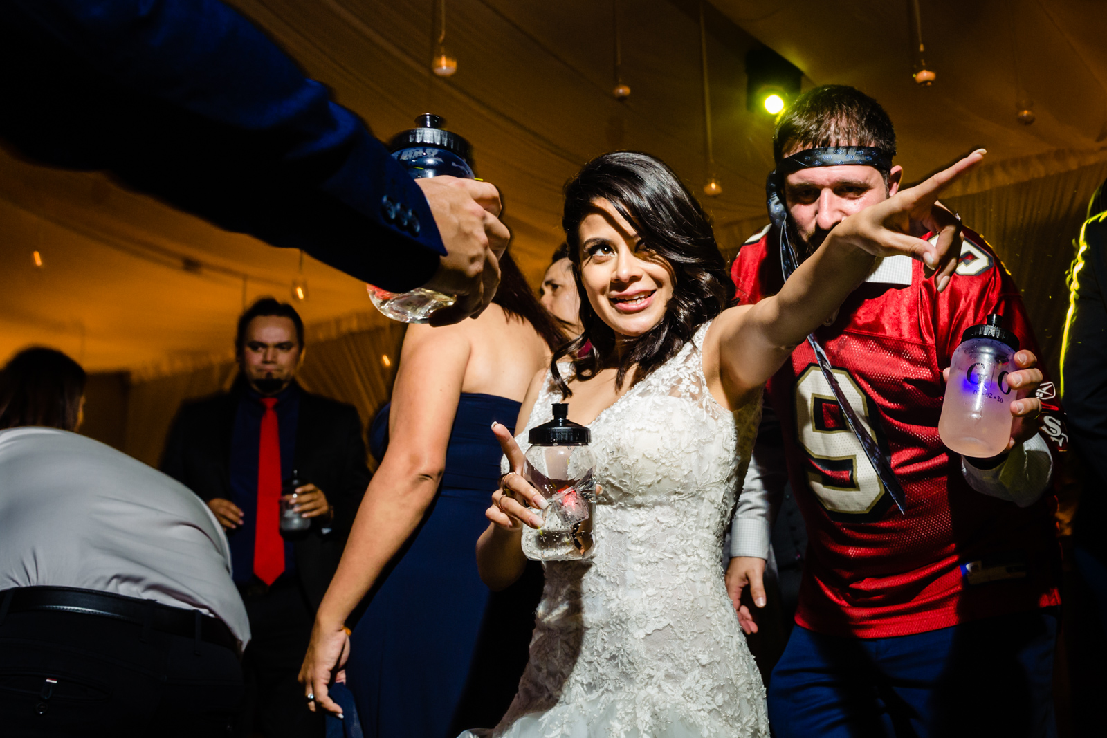 bride having fun on the dance floor dancing and drinking with friends