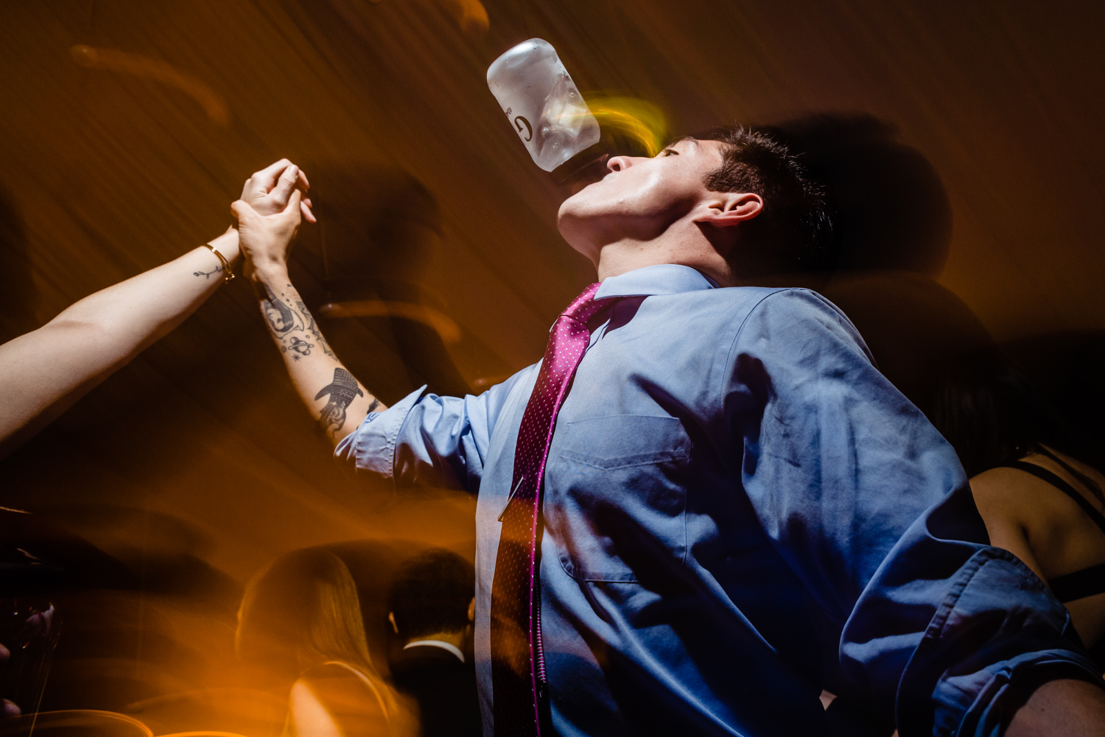 guy drink o the dance floor with drink on his mouth