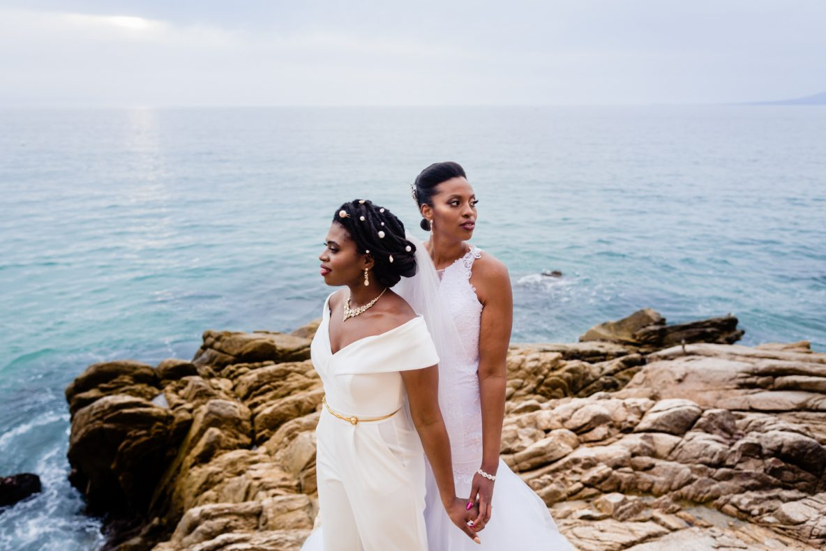 brides holding hands with ocean o the background during the sunset time