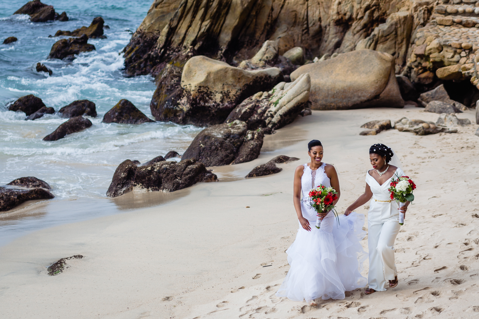 brides are walking together on the beach for go to the ceremony and smiling