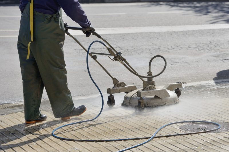 Man pressure washing sidewalk