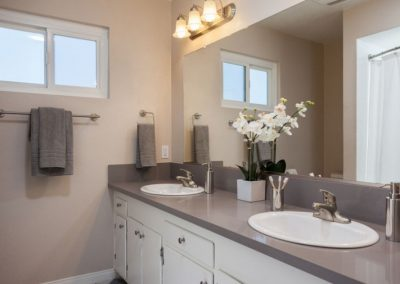 Decorated bathroom with two sinks and a window