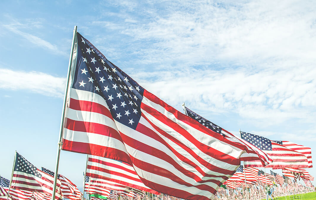 american flags waving on the blue sky