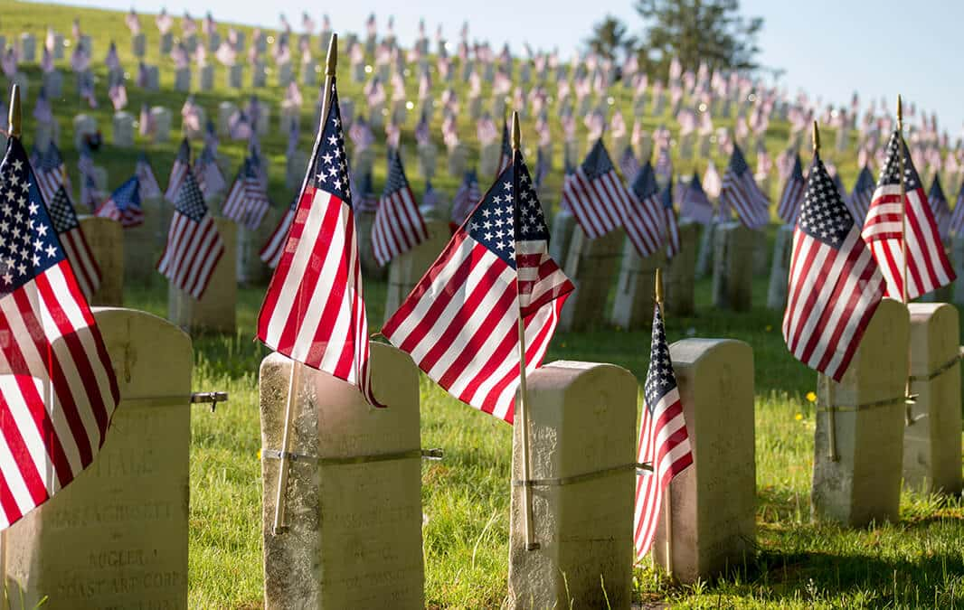 Small American flags and headstones at National cemetery
