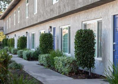 Walkway in front of apartment with blue door