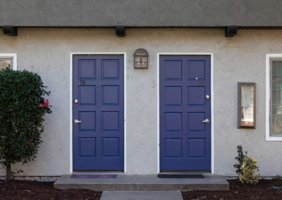 Two blue front doors next to each other