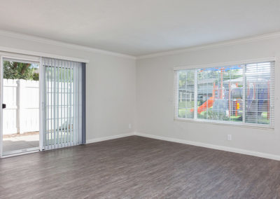 Empty living area with view of playground and patio