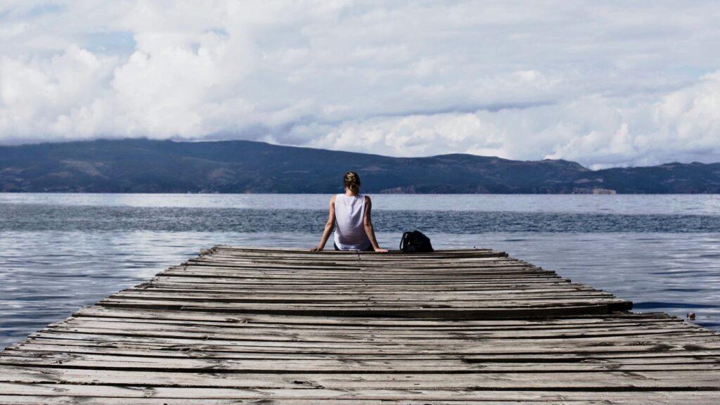 woman sitting on dock of lake