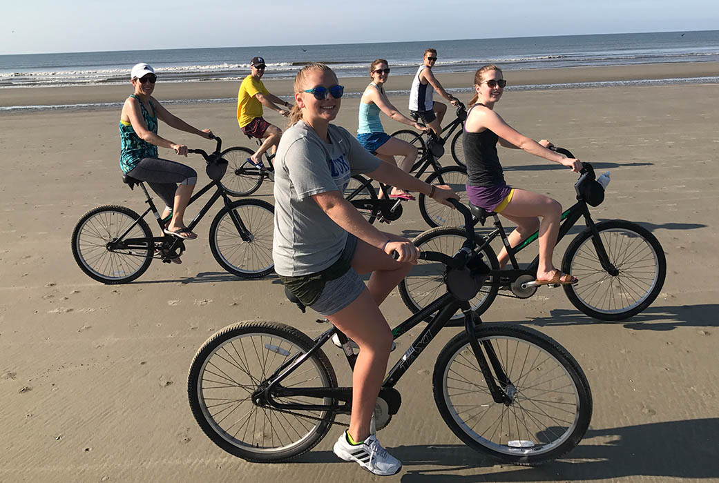 The Brown family riding bikes on the beach