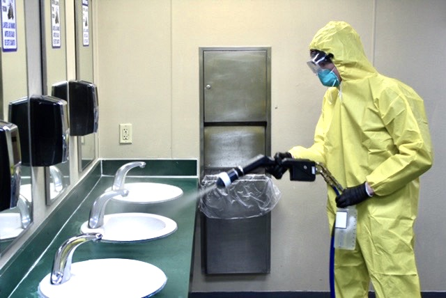 Man spraying disinfectant in restroom