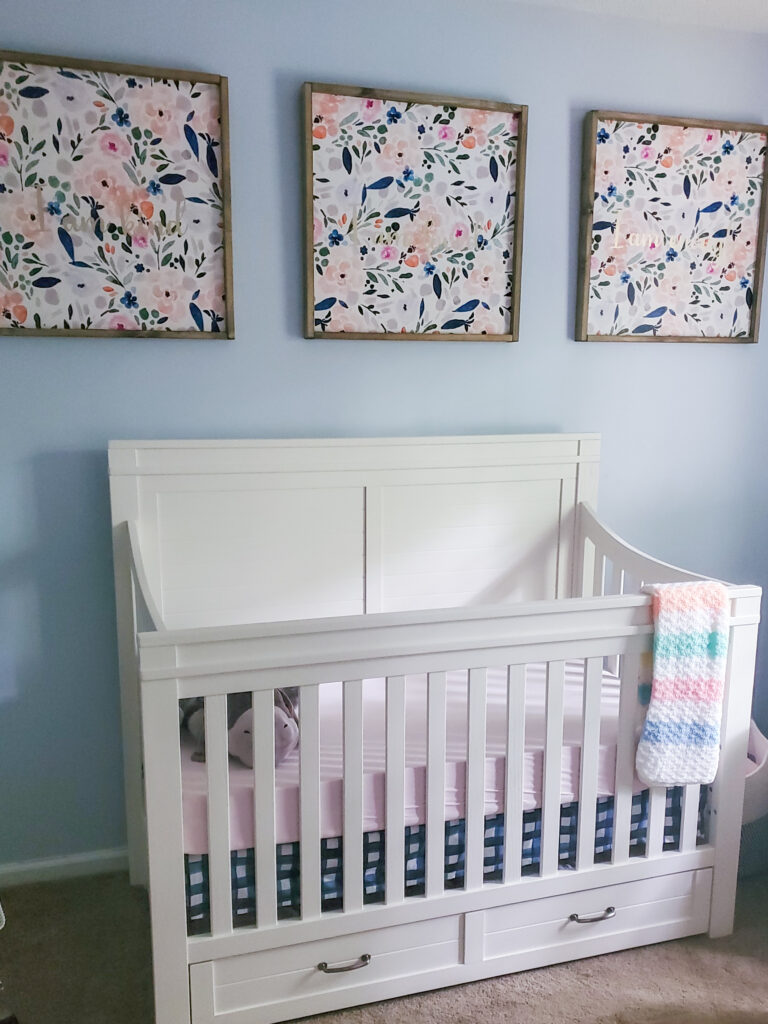 baby girl nursery with white crib and watercolor floral signs