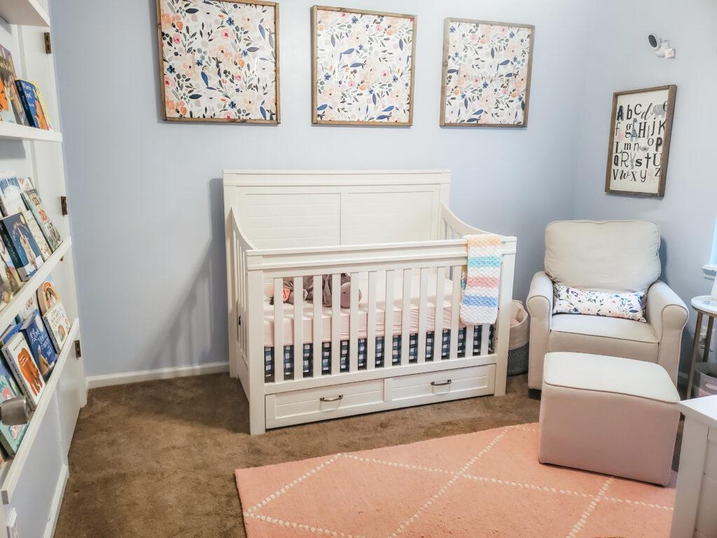 baby girl nursery with white crib and cream glider