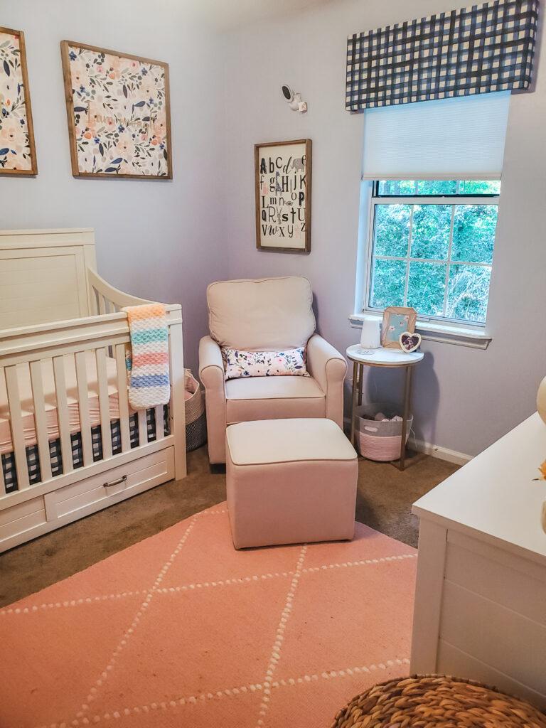 baby girl nursery with cream glider
