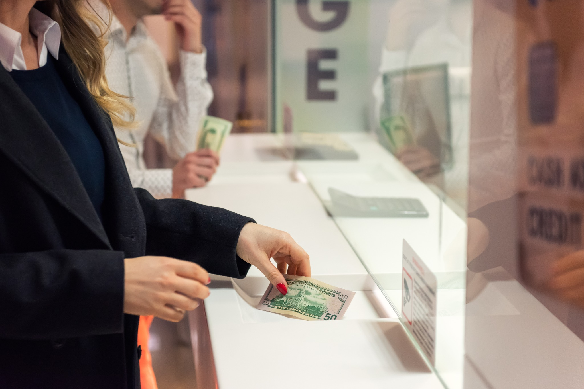 A customer getting money from a teller at a bank