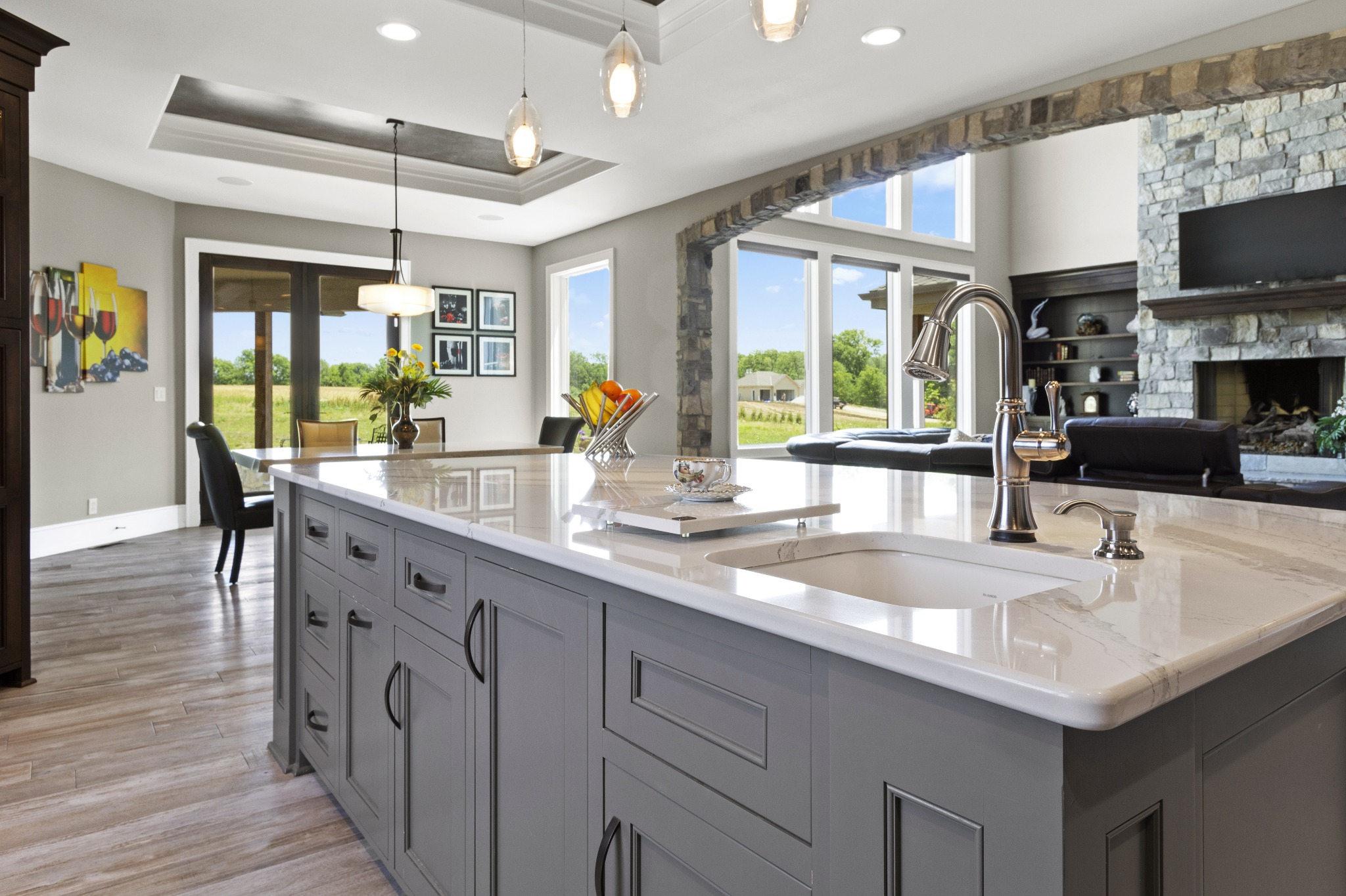 A luxury kitchen with gray cabinets and stone counters.