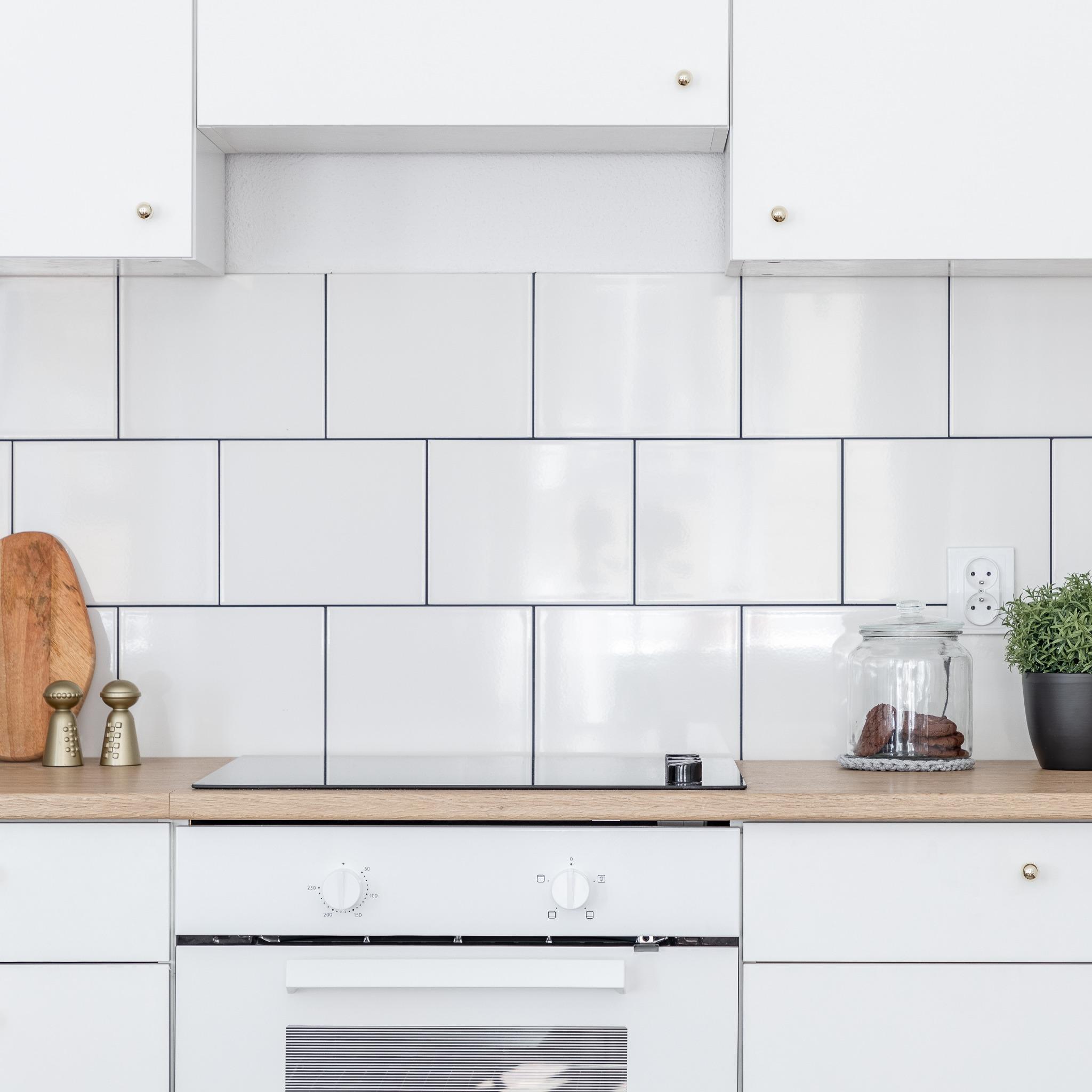 A white kitchen with a square tile backsplash/